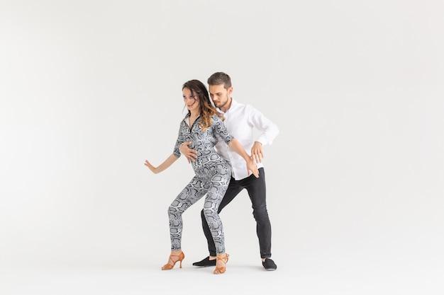 Dança social, kizomba, tango, salsa, conceito de pessoas - lindo casal dançando bachata no fundo branco com espaço de cópia