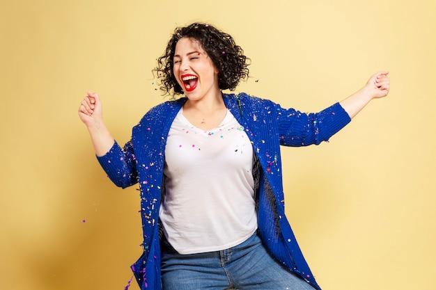 Dançando e rindo mulher jovem e bonita mais tamanho em jeans e um suéter azul. parede amarela.