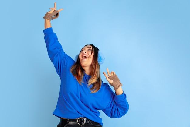 Dançando. retrato de uma mulher caucasiana sobre fundo azul do estúdio. linda modelo feminino com roupas quentes. conceito de emoções humanas, expressão facial, vendas, anúncio. clima de inverno, época de natal, feriados.