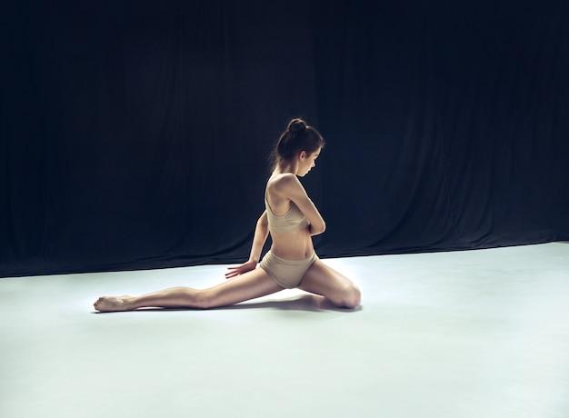 Dançarina adolescente dançando no estúdio de chão branco.