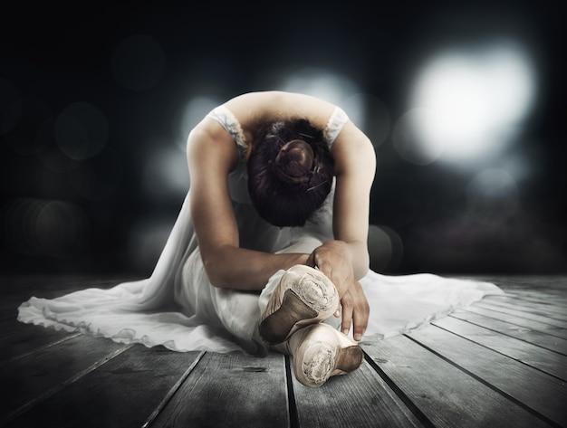 Dançarina clássica fazendo alongamento em um palco de teatro
