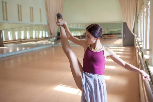 Dançarina de balé clássico posando no barre na sala de ensaio