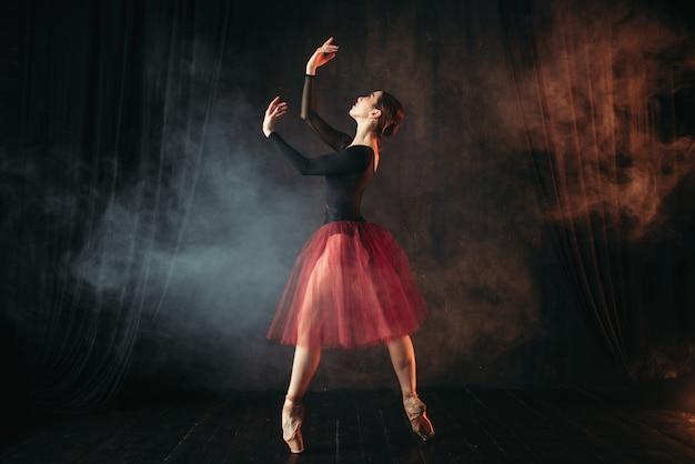 Dançarina de balé com vestido vermelho dançando no palco