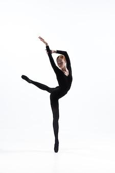 Dançarina de balé jovem e graciosa no estilo preto mínimo, isolado no fundo branco do estúdio.