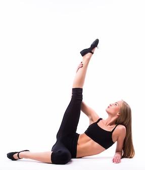 Dançarina de balé linda caucasiana alta, alongando-se e aquecendo a parede branca isolada de corpo inteiro