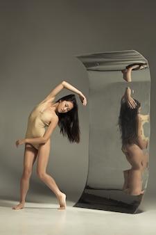 Dançarina de balé moderno jovem e elegante em marrom com espelho