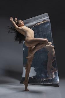 Dançarina de balé moderno jovem e elegante na parede cinza com o espelho e reflexos de ilusão na superfície