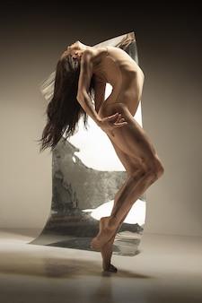 Dançarina de balé moderno jovem e elegante na parede marrom com o espelho e reflexos de ilusão na superfície