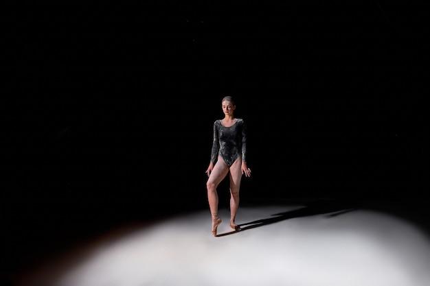 Dançarina de balé posando em pontos, preparada para dançar sozinha, em estúdio em fundo preto do estúdio. retrato de corpo inteiro senhora em farinha, ginástica e conceito de balé. elegante e lindo