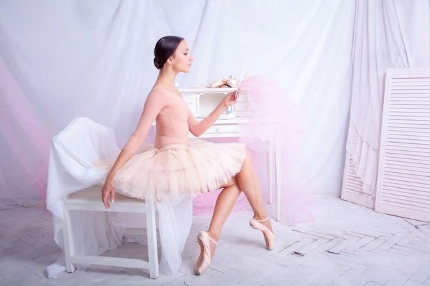 Dançarina de balé profissional, olhando no espelho rosa