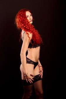 Dançarina de cabaré ruiva sexy em lingerie em uma parede escura, espaço livre para seu texto