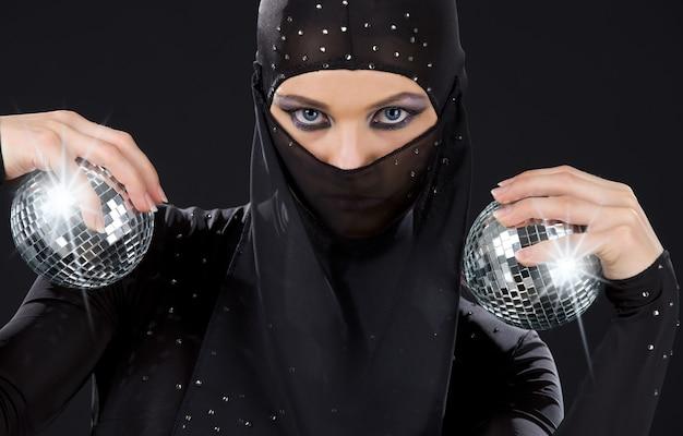 Dançarina de festa com vestido ninja e bolas de discoteca