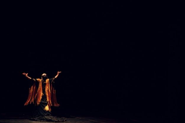 Dançarina de flamenco em traje tradicional. dança espanhola de flamenco no palco. copie o espaço.