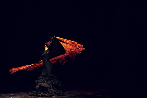 Dançarina de flamenco em traje tradicional. dança espanhola de flamenco no palco.
