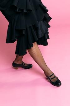 Dançarina de flamenco posando de pernas em fundo rosa