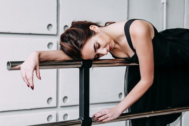 Dançarina de menina bonita. dançarina de garota cansada. bailarina menina ou dançarina em um vestido preto, deitado em uma barra de balé