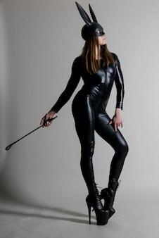 Dançarina de mulher sexy linda posando com fantasia de látex e máscara de coelho preto com chicote no fundo. conceito de coelhinho da páscoa.