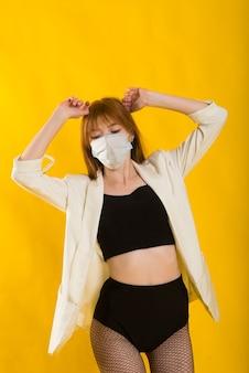 Dançarina de strip-tease em amarelo com máscara protetora de macacão preto