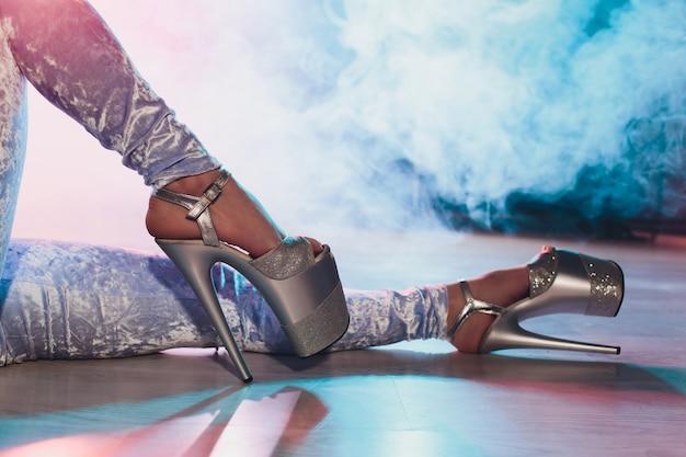 Dançarina de strip-tease jovem movendo-se em sapatos de salto alto no palco na boate de strip, dança do poste.