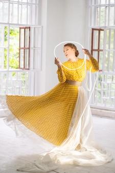 Dançarina de vestido amarelo faz pa segurando um círculo brilhante nas mãos dela.