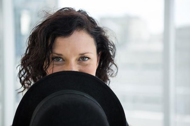Dançarina, escondendo o rosto com chapéu