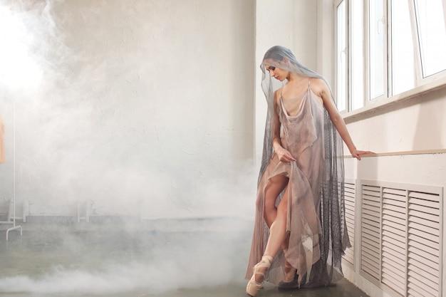 Dançarina feminina posa em um vestido longo bege com fumaça no fundo no estúdio