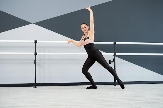 Dançarina feminina treinando em grande salão com corrimãos
