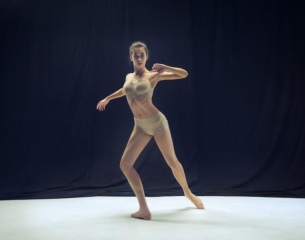 Dançarina jovem adolescente dançando no fundo do estúdio de piso branco. projeto de bailarina.