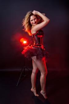 Dançarina loira burlesca de vestido curto, fundo preto, no palco