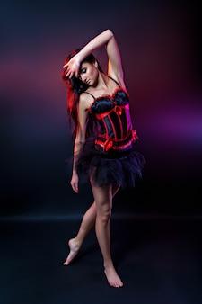 Dançarina morena burlesca em vestido curto, fundo lila, no palco