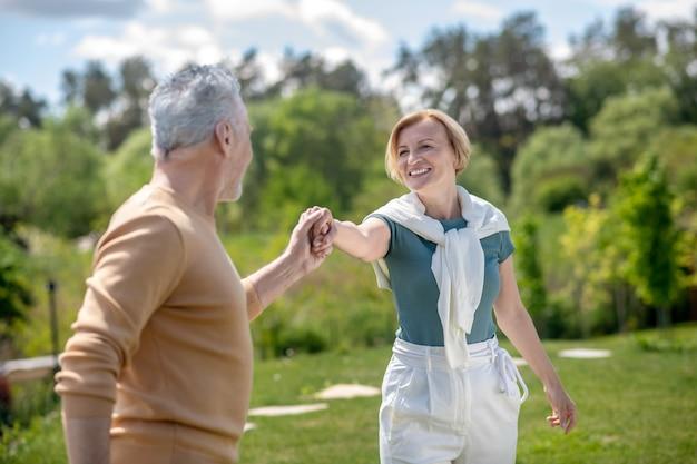Dançarina pegando uma senhora loira satisfeita pela mão