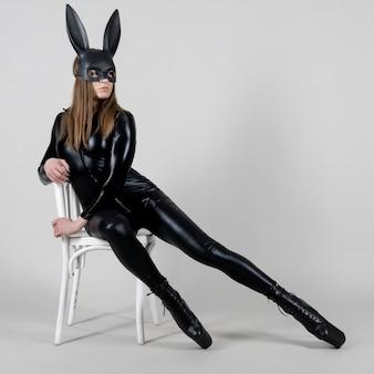 Dançarina sexy de mulher bonita posando com fantasia de látex no fundo. conceito de coelhinho da páscoa.