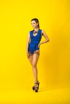 Dançarina sexy feminina vestindo macacão azul e salto alto em um fundo amarelo