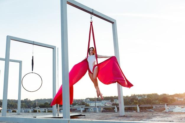 Dançarina sexy que executa dança aérea no telhado ao pôr do sol