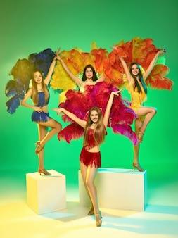 Dançarinas posando na parede verde