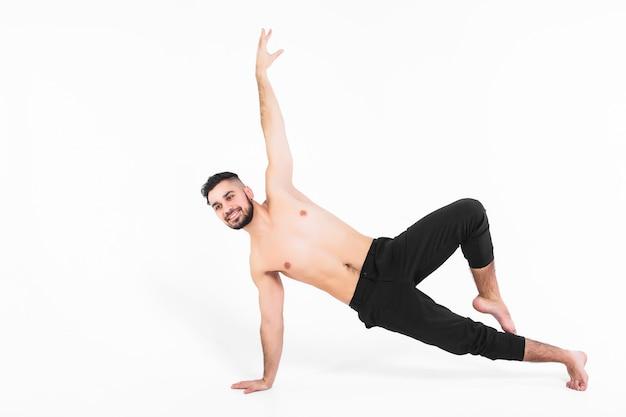 Dançarino de balé jovem e bonito nos truques brancos, modernos.