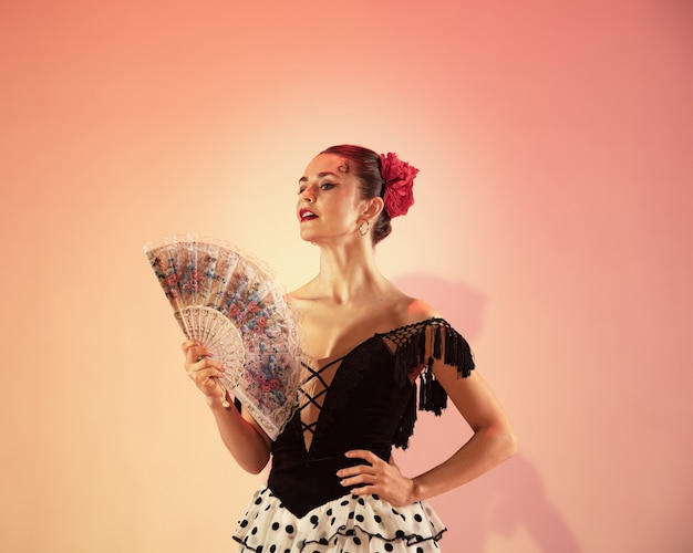 Dançarino de flamenco. espanha mulher cigana com rosa vermelha e ventilador de mão espanhol posando e dançando no estúdio. temperamento espanhol apaixonado e paixão pela dança. conceito de emoções humanas