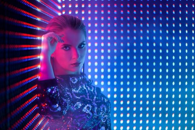 Dançarino do disco na luz de néon no clube nocturno. moda modelo mulher em luz néon