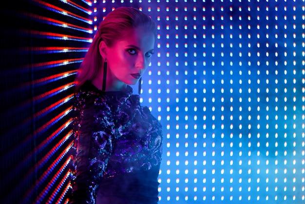 Dançarino do disco na luz de néon no clube nocturno.