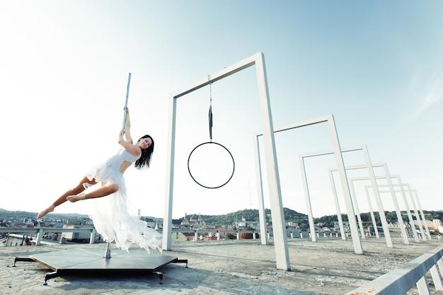 Dançarino sexy bonito do poste que executa no terraço ao ar livre