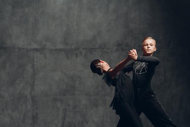 Dançarinos de tango em pares em traje preto dançando no salão de baile.
