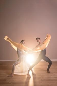 Dançarinos de vista frontal segurando um pano