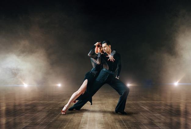 Dançarinos elegantes em trajes, dança ballrom no palco do teatro. parceiros femininos e masculinos em pares profissionais dançando na cena