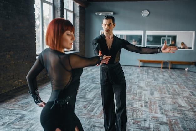 Dançarinos em fantasias no treinamento de dança ballrom em classe. parceiros masculinos e femininos em pares profissionais dançando no estúdio