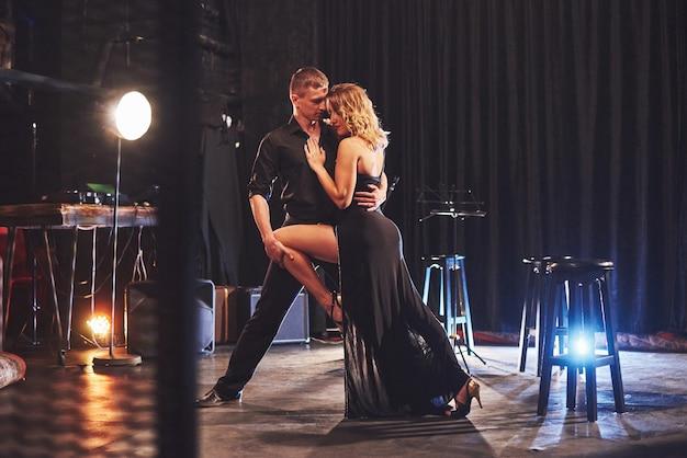 Dançarinos habilidosos se apresentando em um quarto escuro sob a luz.