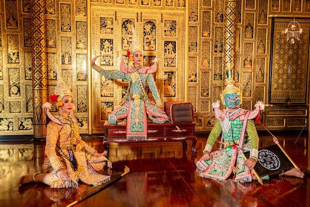 Dançarinos típicos da tailândia com roupas típicas em fundo de paredes douradas