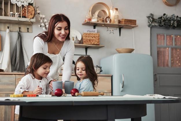 Dando algo delicioso. jovem mulher bonita dar as crianças bebidas enquanto eles sentados perto da mesa com brinquedos