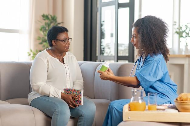 Dando alguns comprimidos. senhora idosa de pele escura doente olhando para uma jovem enfermeira carinhosa dando-lhe alguns comprimidos