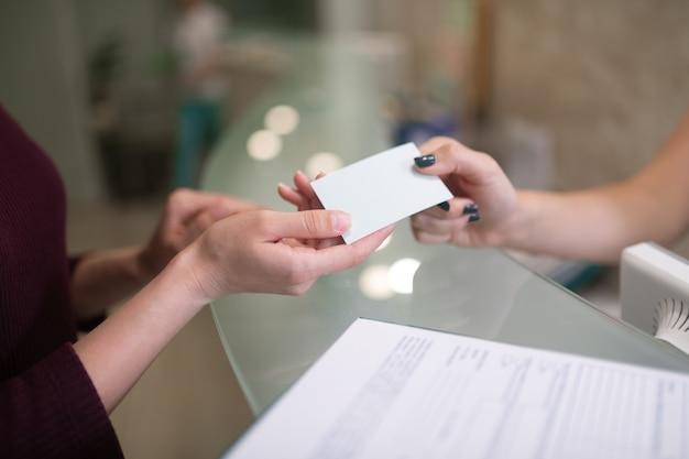 Dando cartão de nome. close de recepcionista prestativa dando o cartão de visita do dentista para o cliente