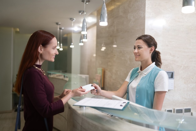 Dando detalhes de contato. recepcionista sorridente de odontologia dando detalhes de contato para o cliente após o exame